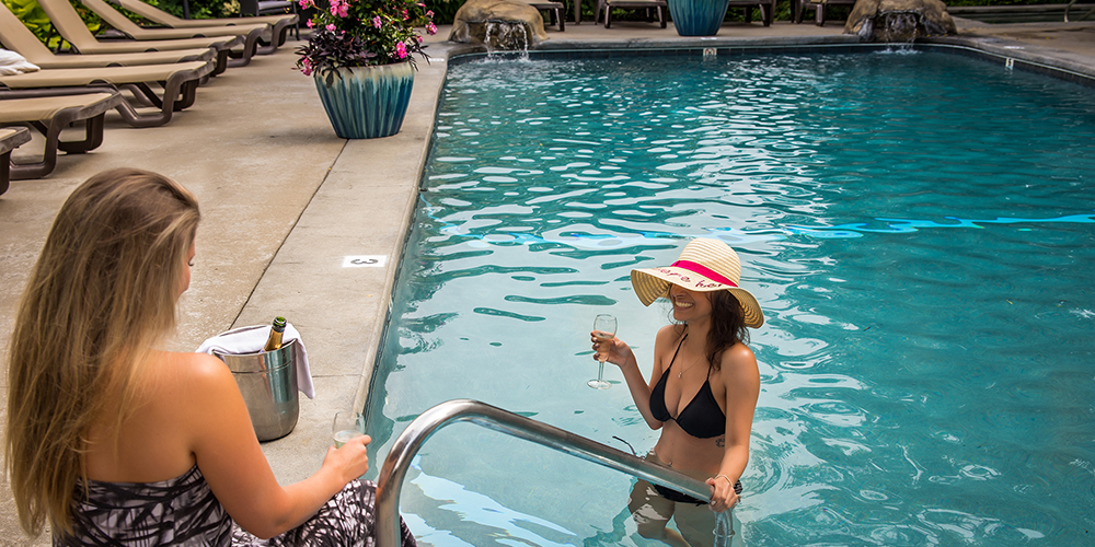 Guests enjoying the seasonal outdoor pool at the Dan'l Webster Inn & Spa